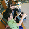 Record-Eagle/Keith King<br /> Malcom Mahler, 8, of Traverse City, uses his iPad 2 alongside his mother, Heidi Mahler, at the Traverse Area District Library on Woodmere Avenue.