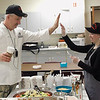 Record-Eagle/Jan-Michael Stump<br /> Grand Traverse Resort executive sous chef Bill Matthews, left, high-fives Elk Rapids High School lifeskills student Samantha Trout, 16, as they put the finishing touches on Friday's faculty lunch. The class, a special education class new this year at the school focusing on lifelong functional skills, prepared lunch for faculty Friday with the help of Matthews. The menu included meat and vegetarian lasagna, antipasta salad, garlic bread and chocolate-dipped spumoni for dessert.