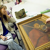Record-Eagle/Jan-Michael Stump<br /> Paula Lewis, of Traverse City, reacts after a painting she bought for $10 at a garage sale was appraised by Don Butkovich for $500 at Dennos Museum.