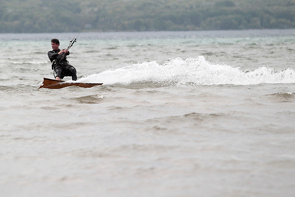 Record-Eagle/Jan-Michael Stump<br /> Eric Nuffer, of Williamsburg, cruises across East Grand Traverse Bay Tuesday on his kiteboard off Bayside Park in Acme.