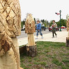 Record-Eagle/Keith King<br /> Traci Bostick, of Mesick, and her son Rigz Bostick, 13, walk past chainsaw-carved morel mushrooms Saturday during the annual Mesick Mushroom Festival. The carvings were done by John Wetterman, of Manton, using storm-damaged popple trees.