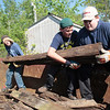 Record-Eagle/Jan-Michael Stump<br /> Traverse City West Middle School eighth-graders, from left, Trystaun Bullard, Kellen Blackburn and Eric Boglan stack a railroad tie in a dumpster during Thursday's Project Greenagers 2012 on the Leelanau Trail between Grandview and Carter Roads in Greilickville. American Waste Recycling and Team Elmers donated time and equipment to help haul away the ties, left from when the rail line became a trail in the early 1980s, because of the potential for industrial preservatives used to treat the wood to leak into nearby wetlands. Other student groups from the school did work in the DeYoung Natural Area, Port Oneida and several other locations around Leelanau County.