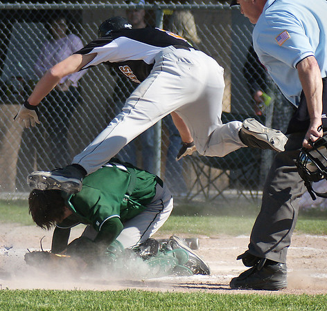 Record-Eagle/ Keith King<br /> Central's Brandon Harrison leaps over West catcher Ryan Ellsworth to score a run in a baseball game between the two schools. The Trojans swept the doubleheaders.