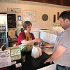 "Record-Eagle Photo/Art Bukowski<br /> Darlene Renzema helps a customer at the Elk Rapids Sweet Shop. ""There's still a lot of unanswered questions for everyone,"" she said."
