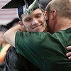 Record-Eagle/Douglas Tesner<br /> Don Gatrell grabs his son, Branden, for a hug during the processional of Northwestern Michigan College's commencement ceremony at Traverse City Central High School on Saturday.