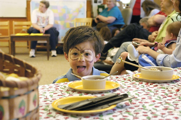Record-Eagle/Lisa Perkins<br /> Three-year-old Keaton LaCross licks his lips, anticipating a taste of locally produced honey during a beekeeping program held Saturday at Peninsula Community Library.