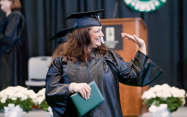 Record-Eagle/Douglas Tesner<br /> NMC graduate Shannon Smith waives to the crowd during Saturday's commencement ceremony at Traverse City Central High School.