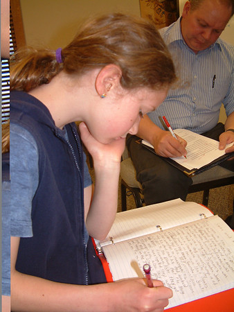 """Record-Eagle/Marta Hepler Drahos<br /> Johanna Johnson, 10, works on a short story while her father, Tom Johnson, critiques a submission for West Side Writers' first project, a church booklet to be called """"The Fruits of the Spirit."""""""