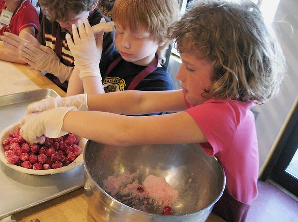 Record-Eagle/Jodee Taylor<br /> Paige Fischer, right, fills a pie shell with cherries while Asher Lucas-Cuddeback watches during a Junior Achievement field trip to Grand Traverse Pie Co. Second-graders from Central Grade School were learning about unit production.