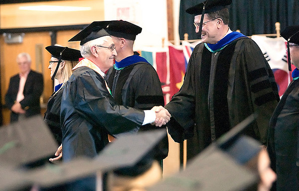 Record-Eagle/Douglas Tesner<br /> Luc Serriere, left, NMC's oldest graduate with honors, shakes hands with NMC Trustee Doug Bishop before receiving his diploma.
