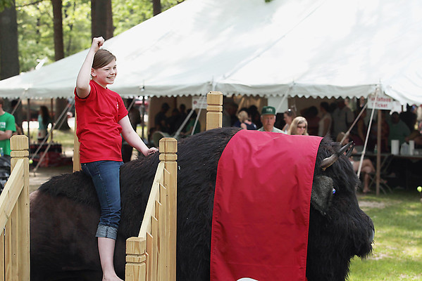 """Record-Eagle/Keith King<br /> Callie Wyers, 12, of Traverse City, poses for a photograph while sitting on """"Chip,"""" a faux buffalo."""