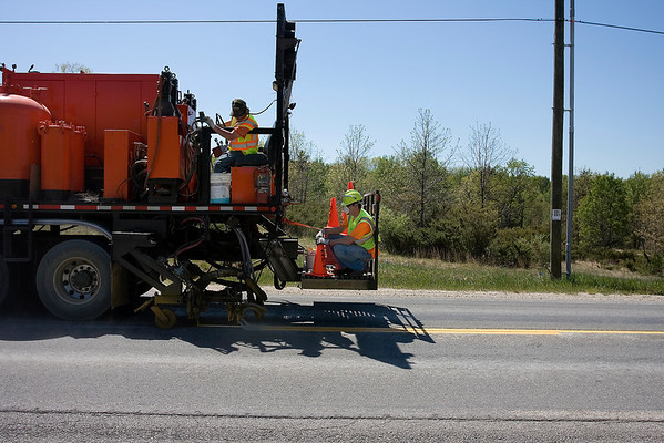 """Record-Eagle/ Keith King<br /> Workers from P.K. Contracting apply a special paint to a section of Five Mile Road after grinding off the previous lane markings.<br /> The Grand Traverse County Road Commission used $278,000 in federal stimulus funds to pay for the special paint that adheres like an epoxy and should last three years. The road commission warns motorists to beware of paint overspray in work areas. The paint, which dries in three to four minutes, requires professional repair to remove from vehicles. Motorists can expect delays in work areas on East Bay and Garfield Township roads through June 18. Updates on work area locations are available at  <a href=""""http://www.gtcrc.org"""">http://www.gtcrc.org</a>."""