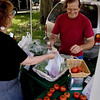 Record-Eagle/ Keith King<br /> Left, Marsha Minervini, of Traverse City, purchases tomatoes from Richard Jelenek, of Buckley, on Friday during the Village Outdoor Farmers Market at the Village at Grand Traverse Commons.