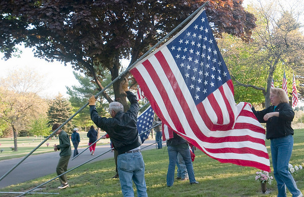 Record-Eagle/Douglas Tesner<br /> Bill and Stephanie Loomis, other volunteers, and VFW members raise flags at Grand Traverse Memorial Gardens Cemetery in Traverse City. The flags are raised and lowered Saturday, Sunday and today, Memorial Day.