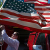 Record-Eagle/Jan-Michael Stump<br /> Lt. Barney Barber of the South Torch Lake Fire Department attaches a flag to one of the department's trucks before the start of Monday's Alden Memorial Day parade.