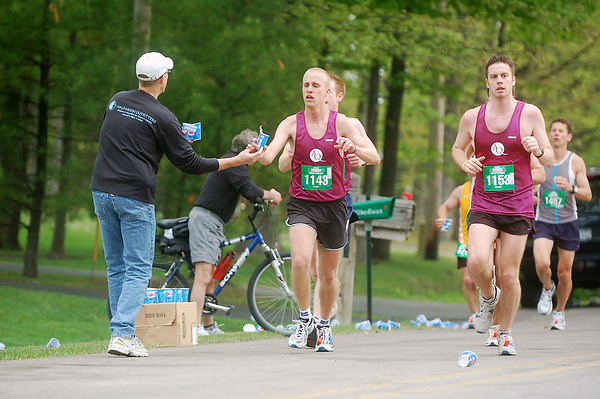 Record-Eagle/Sarah Brower<br /> Volunteers hand out water to Bayshore Marathon runners at the race's half-way point.