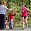 Record-Eagle/Sarah Brower<br /> Oscoda's Christine McKenzie shares high-fives with Shawn Spencer and his son Josh, 8, during Saturday's Traverse City State Bank Bayshore Marathon.