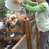 Record-Eagle/Sarah Brower<br /> Annie Hessler, 8, dumps food waste into The Children's House compost site.