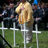 Record-Eagle/Jan-Michael Stump<br /> Patricia Miller, of the VFW Ladies Auxiliaries, lays flowers in front of crosses representing the five branches of service.