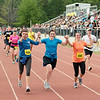 Record-Eagle/Keith King<br /> Runners cross the finish line during the 30th annual Bayshore Marathon on Saturday at Traverse City Central High School.