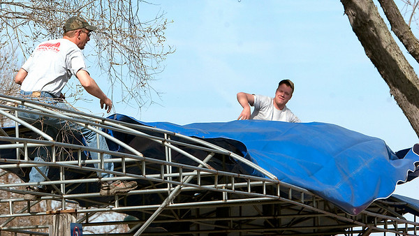 Record-Eagle/Douglas Tesner<br /> Doug Saul and Kody Sheffield, employees of Advance Awnings, install an awning that will shade some of the vendors at the Sara Hardy Downtown Farmers Market, which opens Saturday. 2009 is the market's 25th year.