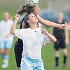 Record-Eagle/Jan-Michael Stump<br /> Elk Rapids' Elin Larsen (17) and Traverse City Liberty's Hélène Dryden (8) fight for the ball in the second half of Thursday's game.