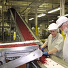 Record-Eagle/Bill O'Brien<br /> Julie Waldecker and Larry Hoffman sort a batch of dried cranberries as they're prepared for packaging at Graceland Fruit Co.'s processing operation in Frankfort.