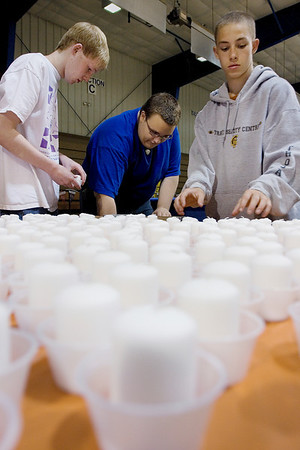 Record-Eagle/ Keith King<br /> From left, volunteers Brian Jurgess, 17, of Fife Lake, Joshua Becker, 17, of Traverse City and Landon Adams, 14, of Traverse City,  place candles in small cups on Friday as they help prepare for the American Cancer Society Relay for Life at the Grand Traverse County Civic Center.