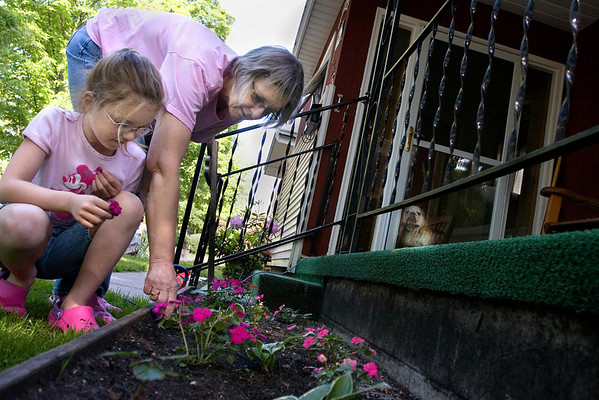 Record-Eagle/ Keith King<br /> Sharon Wood, of Traverse City, weeds in her garden at her home alongside her granddaughter, Marissa Brief, 7, also of Traverse City, as her dog, Maverick, back right, looks on. Maverick was outside with Sharon, but was moved inside when he became too rambunctious.