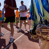 Record-Eagle/ Keith King<br /> Medals for the Bayshore Half Marathon hang from a volunteer's arm, prior to being handed to runners at the finish on the track at the Traverse City Central High School.