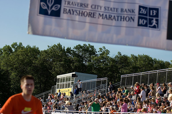 Record-Eagle/ Keith King<br /> A runner crosses the finish line as spectators watch Saturday.
