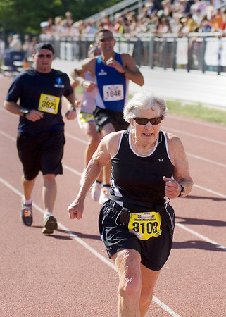 Record-Eagle/ Keith King<br /> Janet Weiler, 74, of Empire, crosses the finish line after running in the half marathon.