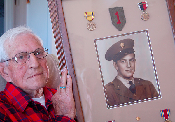 Record-Eagle/Sarah Brower<br /> Clarence Weber, 90, a local World War II veteran, reminisces about living through D-Day. He holds his picture surrounded by medals, taken when he was 25 years old.