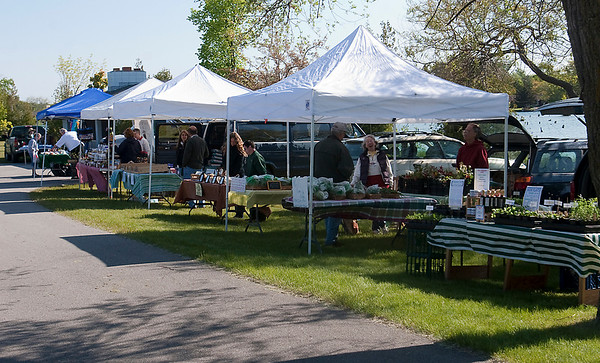 Record-Eagle/Douglas Tesner<br /> Vendors prepare for the farmers market in Elk Rapids. This is the eighth year for the market, which is held at the Chamber building each Friday thru Oct. 30.