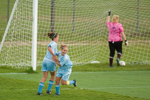 Record-Eagle/Jan-Michael Stump<br /> Liberty's Helene Dryden (8) and Alexandra Michelin (14) celebrate Dryden's goal on Charlevoix goalkeeper Tammy Potter during Tuesday's regional game.