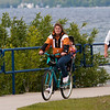 Record-Eagle/Douglas Tesner<br /> Despite cool temperatures and breezy weather, Kathy Younker, her daughter Becca Fiorello, 3, and their friend Blue Quick enjoy some activities on the TART trail going through the Open Space in Traverse City.
