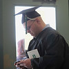 Record-Eagle/Jan-Michael Stump<br /> Northwestern Michigan College student Jason Walter texts his wife before the start of Saturday's Commencement Ceremony in Traverse City Central High School.