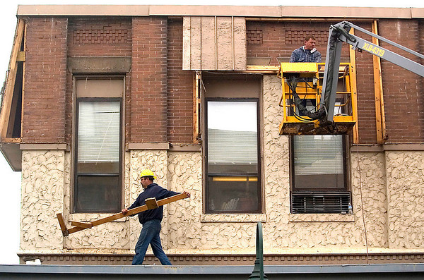 Record-Eagle/Jan-Michael Stump<br /> Earl Steffes, right, and Mark Metts of A. Tanner and Sons, of Walkerville, remove the mansard from the Union Street side of a building at the southwest corner of Union and West Front Streets, revealing the building's original brick.