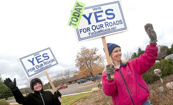 Record-Eagle/Douglas Tesner<br /> Debby Marsh, left, and Renee Kaufman wave to motorists urging them to vote for a millage to repair roads outside the precinct in East Bay Township. Voters soundly defeated the millage request.