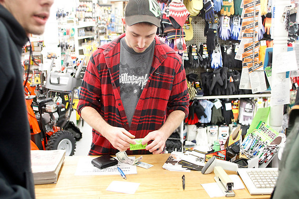 Record-Eagle/Jan-Michael Stump<br /> A.J. Rosinski, of Traverse City, buys his hunting license in preparation for Tuesday's deer opener at Roy's General Store in East Bay Township.