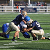 Record-Eagle/Keith King<br /> Traverse City St. Francis defenders Jack Brodeur (41) and Noah LaLonde tackle Ishpeming's Derek Slone on Saturday.