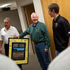 Record-Eagle/Jan-Michael Stump<br /> Traverse City Central's Nick Brunning, right, other teammates and coach Tom Passinault presented Jerry Oleson Jr., left, and Don Oleson with a framed, signed team picture and team golf shirts Wednesday as a thank-you for the brothers' donation that will fund artificial turf at Thirlby Field.