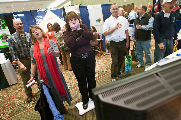 Record-Eagle/Jan-Michael Stump<br /> anet Priest, of Suttons Bay, tries Wii Fitness downhill ski jump at the 7&4 booth with 7&4 commercial production producer Melanie Schmid, left, at the Traverse City Area Chamber of Commerce's Annual Business Expo Tuesday at the Grand Traverse Resort & Spa in Acme. The television station was using the game to help promote its upcoming Winter Olympics coverage.