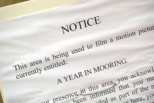 "Record-Eagle/Jan-Michael Stump<br /> A poster gives notice to pedestrians on East Front Street of the filming of a scene for ""A Year in Mooring,"" an independent film being shot in Traverse City."