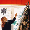 Record-Eagle/Keith King<br /> Keri Fillmore, of Bellaire, hangs Christmas decorations in the storefront of the Sassy Sunflower in downtown Bellaire.