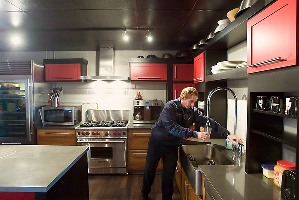 "Record-Eagle/Jan-Michael Stump<br /> Firefighter Chris Jackson gets a glass of water in the newly remodeled kitchen of Station 2. The station's kitchen and lounge received a makeover for a HGTV holiday special ""Carter Comes Home"" with Traverse City native Carter Oosterhouse. It will air on Nov 27."