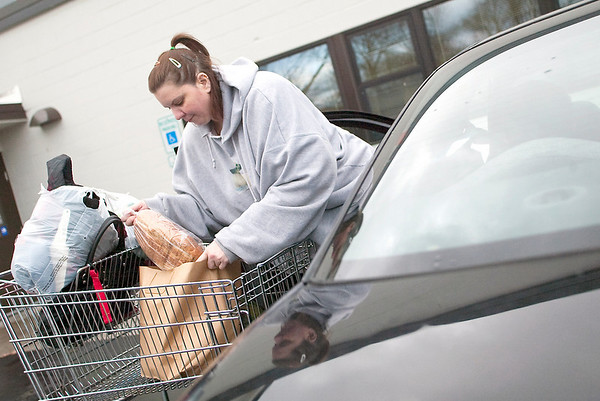 Record-Eagle/Jan-Michael Stump<br /> Julie Compeau loads her Thanksgiving meal package in her car at the Father Fred Foundation on Wednesday morning.