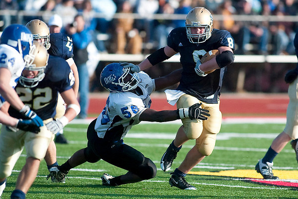 Record-Eagle/Jan-Michael Stump<br /> Traverse City St. Francis fullback Joe Kerridge (8) stiff-arms Ravenna defensive lineman Isiah Dunning (56) in the third quarter of the Glads' Staurday state Division 7 seminfinal win.