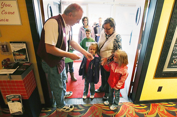 Record-Eagle/Keith King<br /> Volunteer Fred Ray hands bicycle-giveaway tickets to Adrianna Inch, left, 6, of Kentwood, and her sister Allison Inch, 4, who are with their grandmother, Linda Spayth, of Williamsburg, on Saturday.