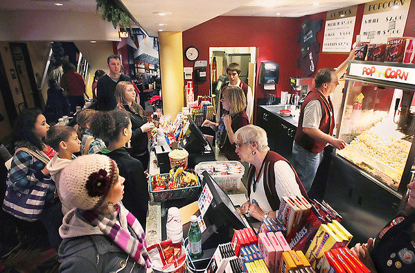 """Record-Eagle/Keith King<br /> Moviegoers stand at the concession counter while volunteers assist Saturday prior to the showing of """"The Wizard of Oz"""" during the 25-Cent Kids Matinee at the State Theatre."""